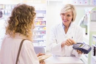 Pharmacist using card machine at pharmacy