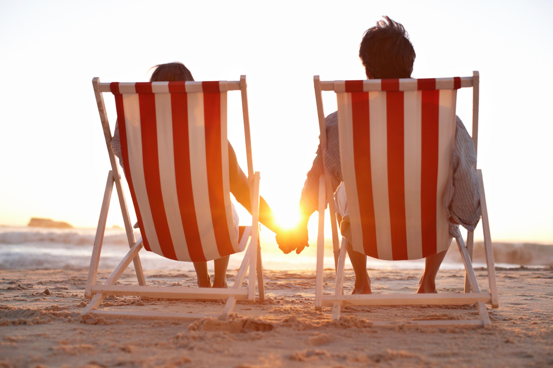 Couple hand in hand sitting on beach.jpg